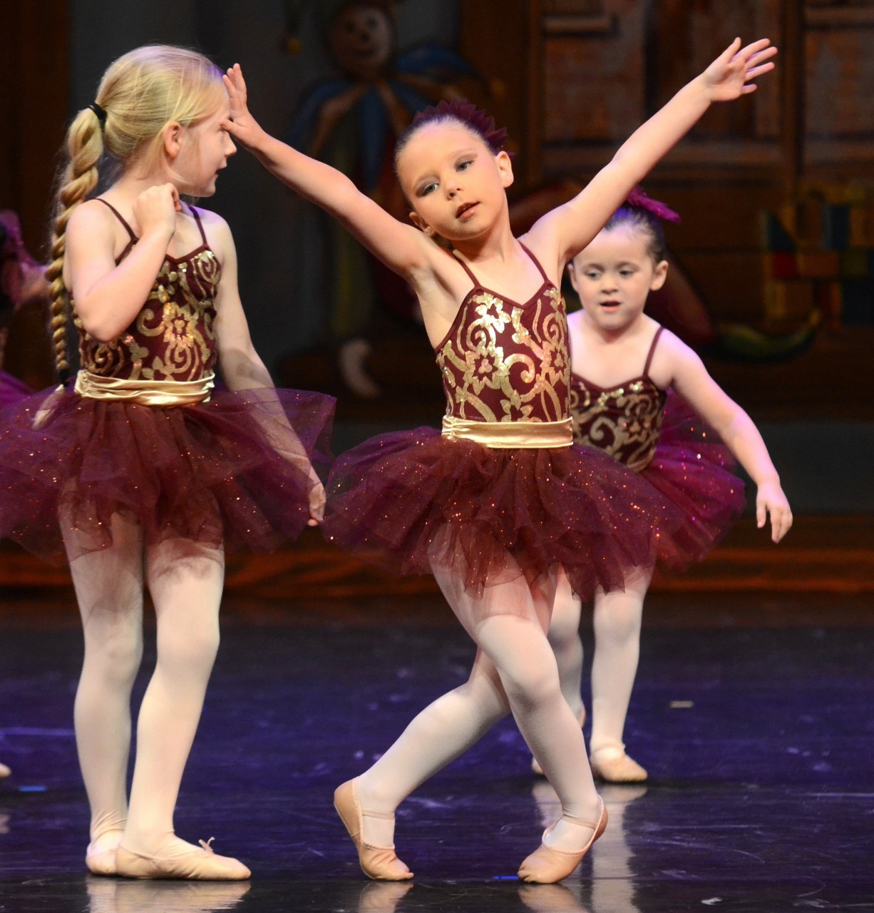 Three white girls dancing on stage in a maroon custom with a tutu, pink tights, and pink ballet shoes