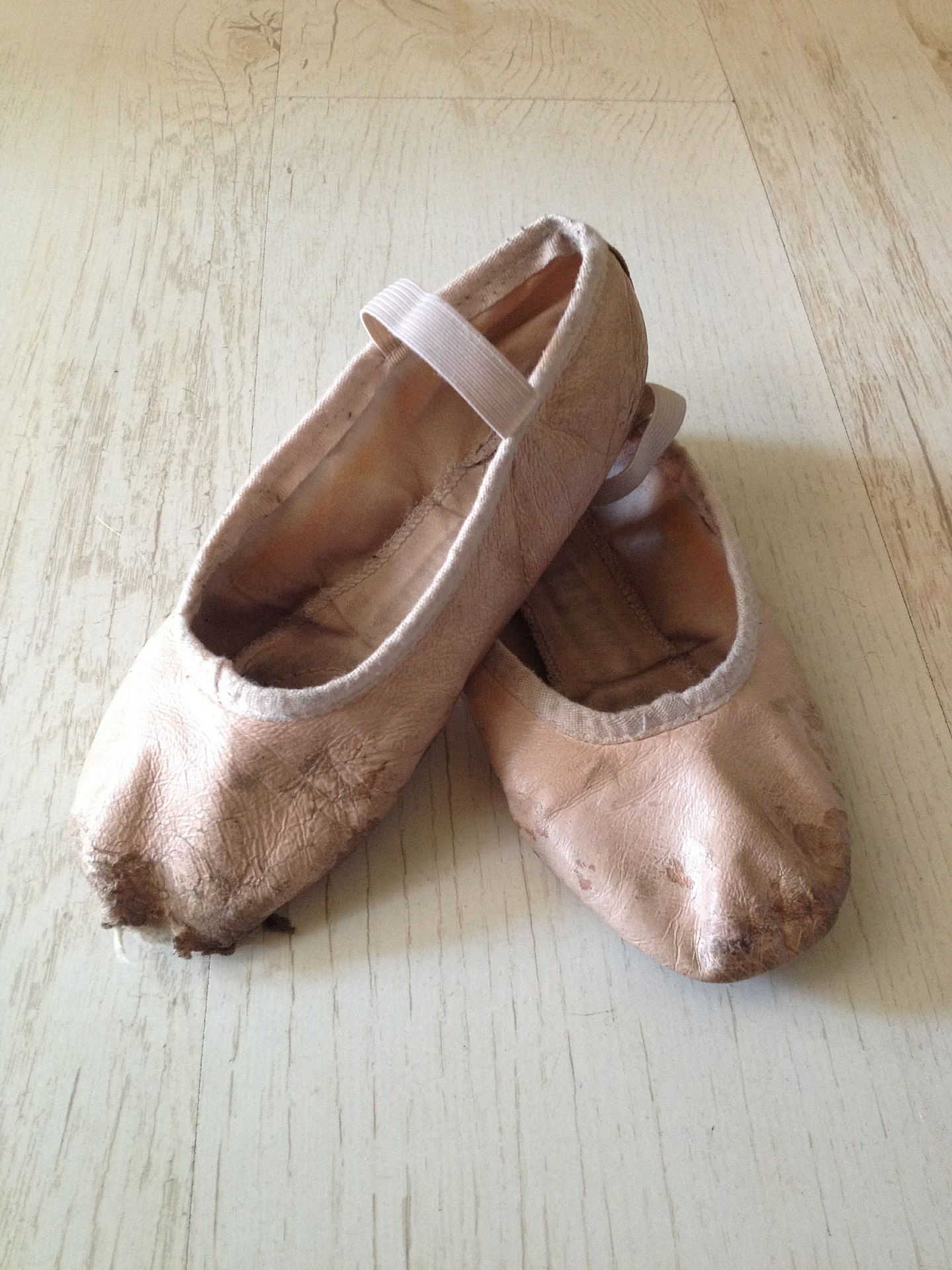 An image of worn pair of pink ballet shoes with a whole in the right foot.