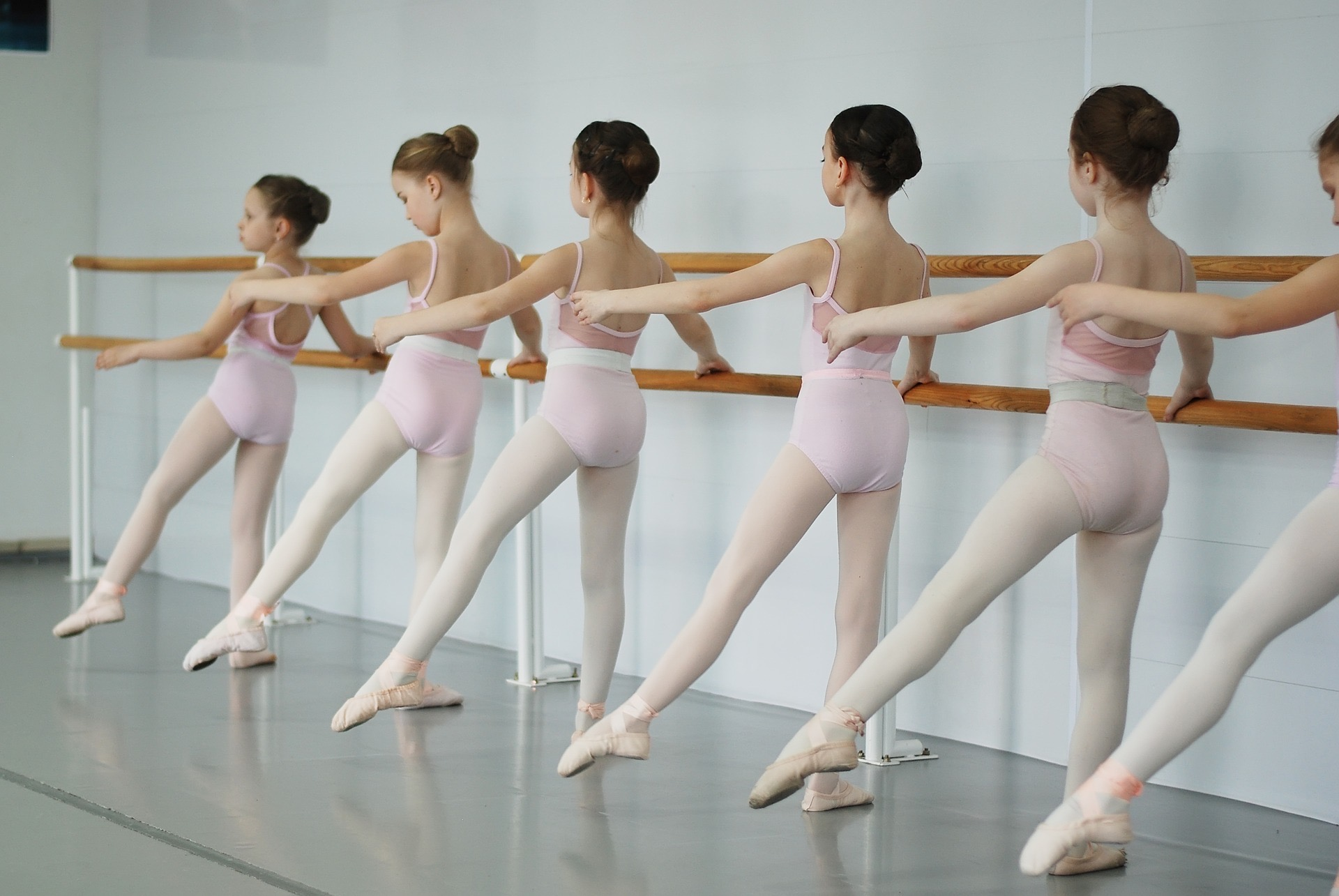 An image of five ballet dancers dancing at a ballet barre. Dressed in pink dance leotards, tights, and ballet shoes.